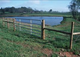 Picture of a pasture with a fence and pond.